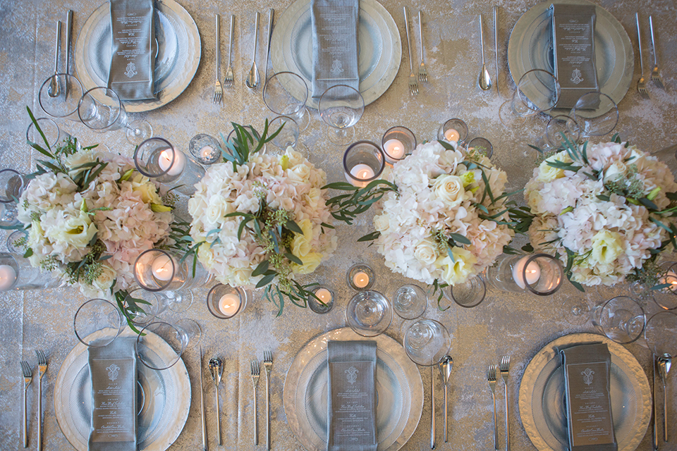 Orange-county-wedding-shoot-at-pasea-hotel-table-set-up-with-silver-table-linen-and-place-settings-with-flower-and-candle-decor